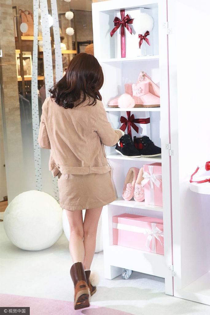 身着卡其色短裙配小夹克,光腿穿大棉鞋可爱十足,抬手秀无名指璀璨钻戒