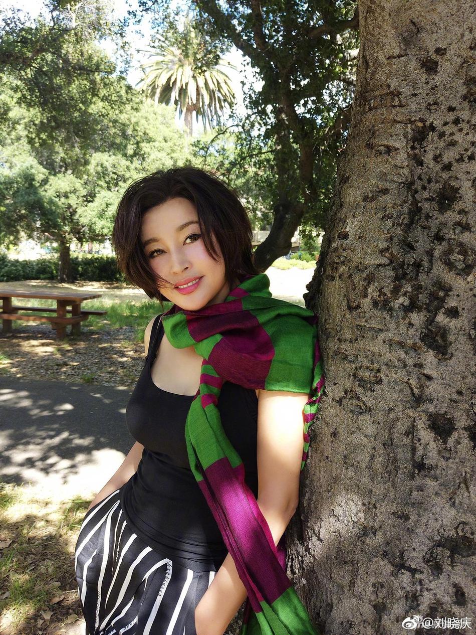 62岁刘晓庆背靠大树凹造型 紧身吊带秀上围图片